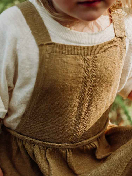 Close up detail on a girls knitted pinafore