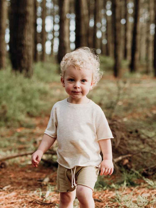 Boy with white hair wearing knitted organic clothes walking in a forest