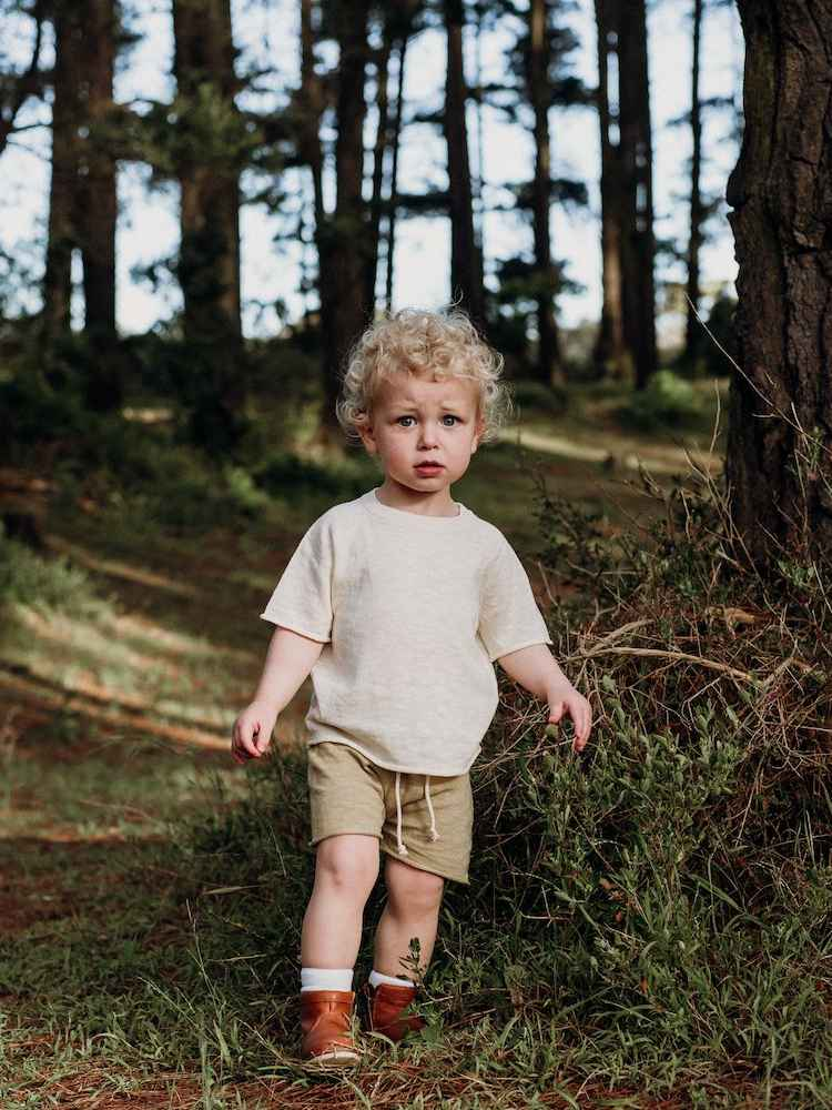 Little boy with blonde curly hair walking through a forest