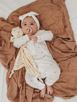 Baby wears the Halo and Horns long sleeved baby white onesie with wheat spot pattern