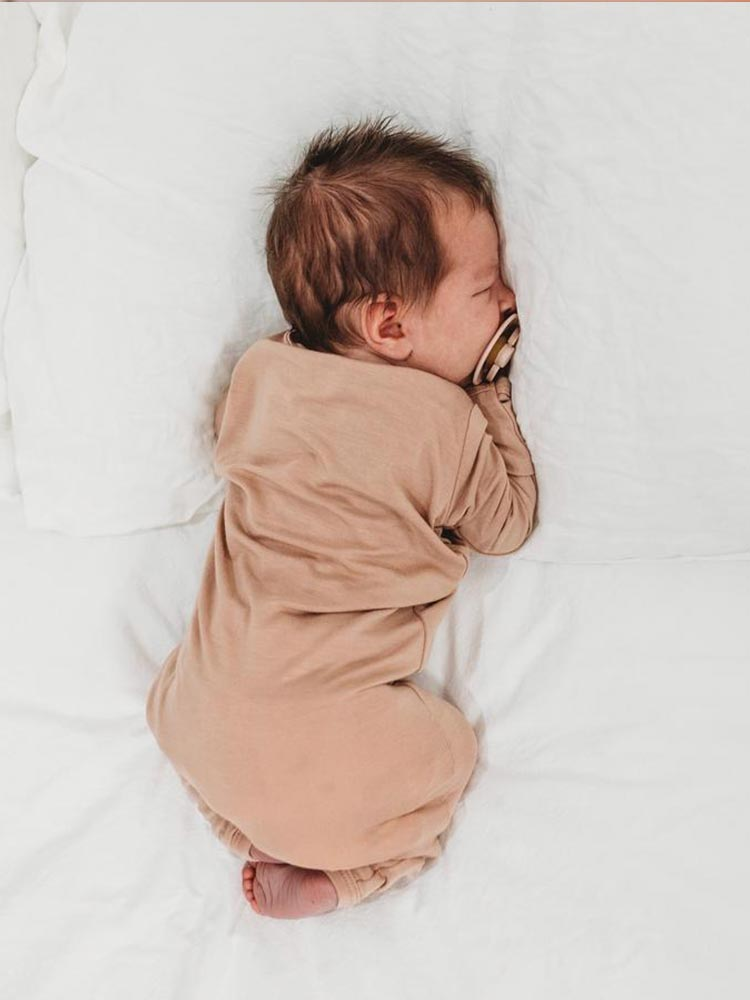 Baby sleeps in a dusty orange coloured onesie by Halo and Horns