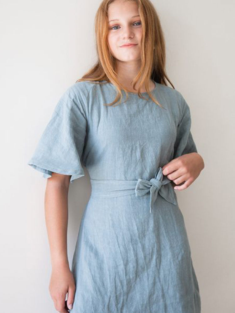 Young girl wears a knee-length light blue linen dress with batwing sleeves and a bow waist tie