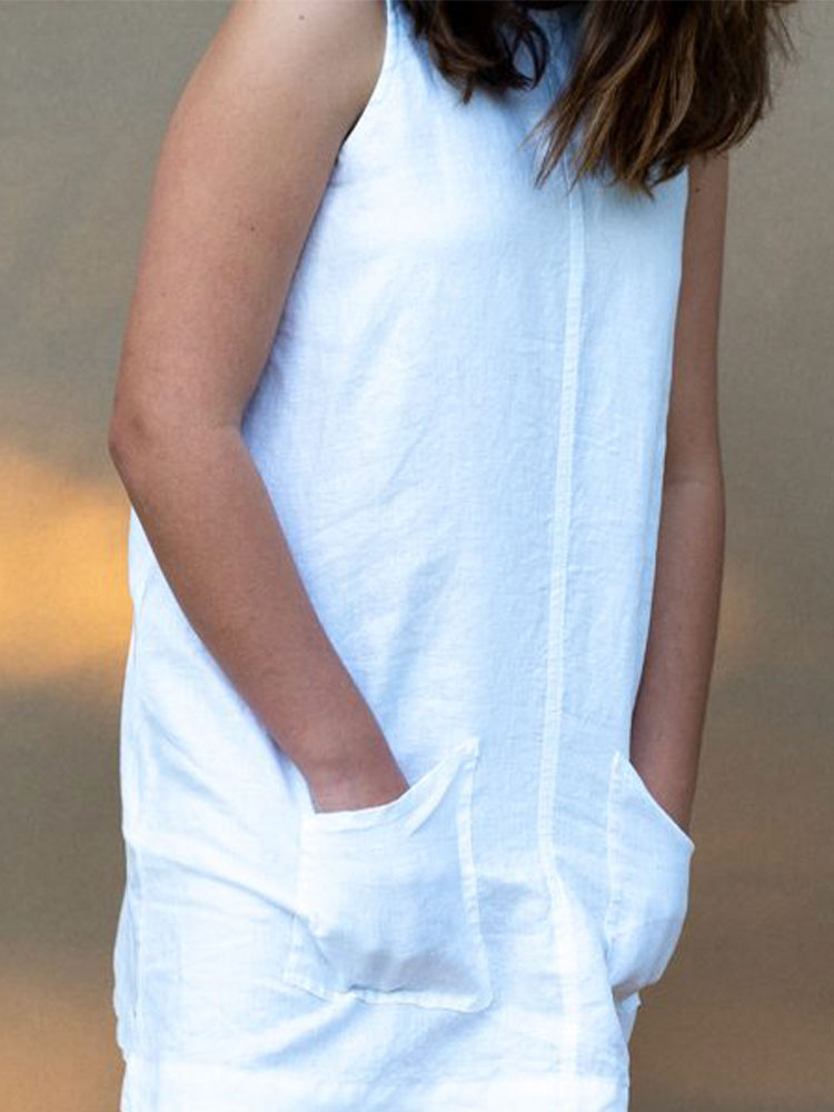 Young girl with her hands in the front pockets of the Hendrik Clothing Co Swing Dress in white linen
