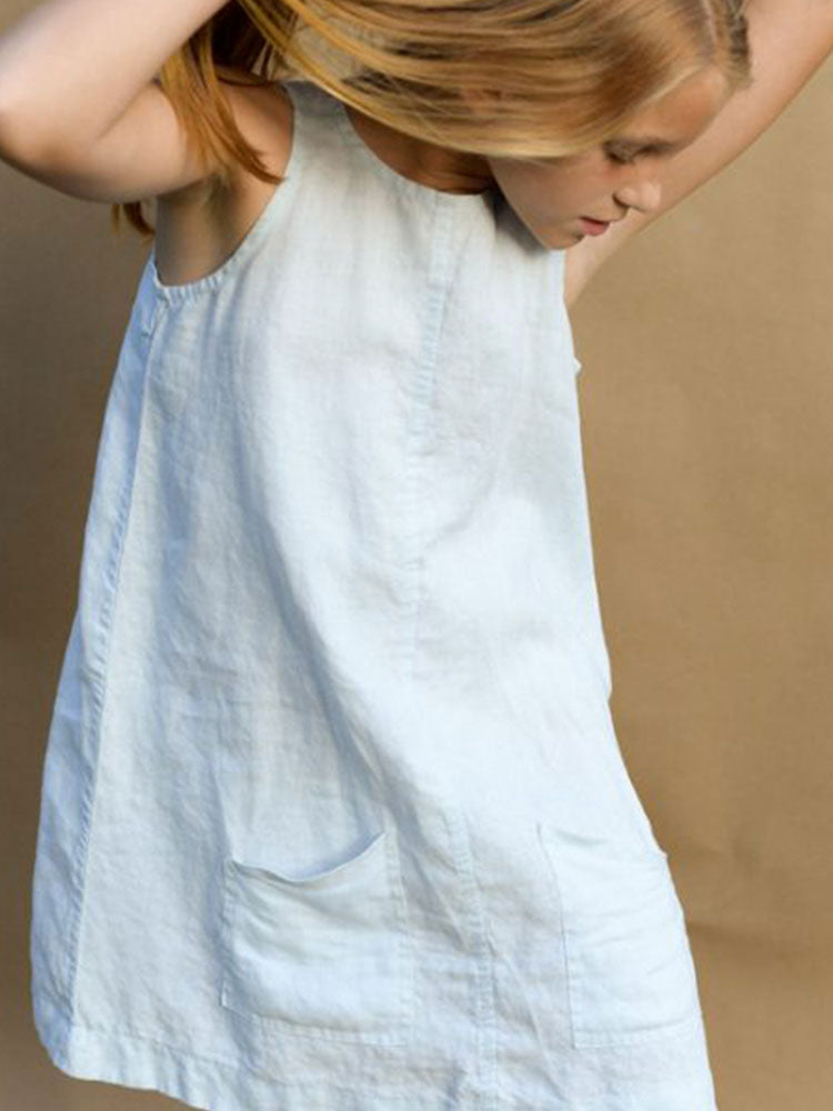 Young girl wears white linen dress with two small pockets in the front