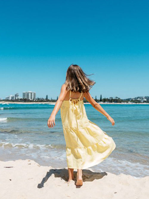Young girl wears the Hendrik Swing Me Around Dress on the beach