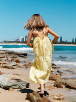 Girl plays on the beach shore in yellow ankle-length Hendrik dress