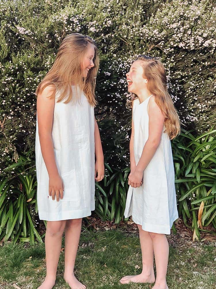Two girls laughing wearing the same dress in front of trees