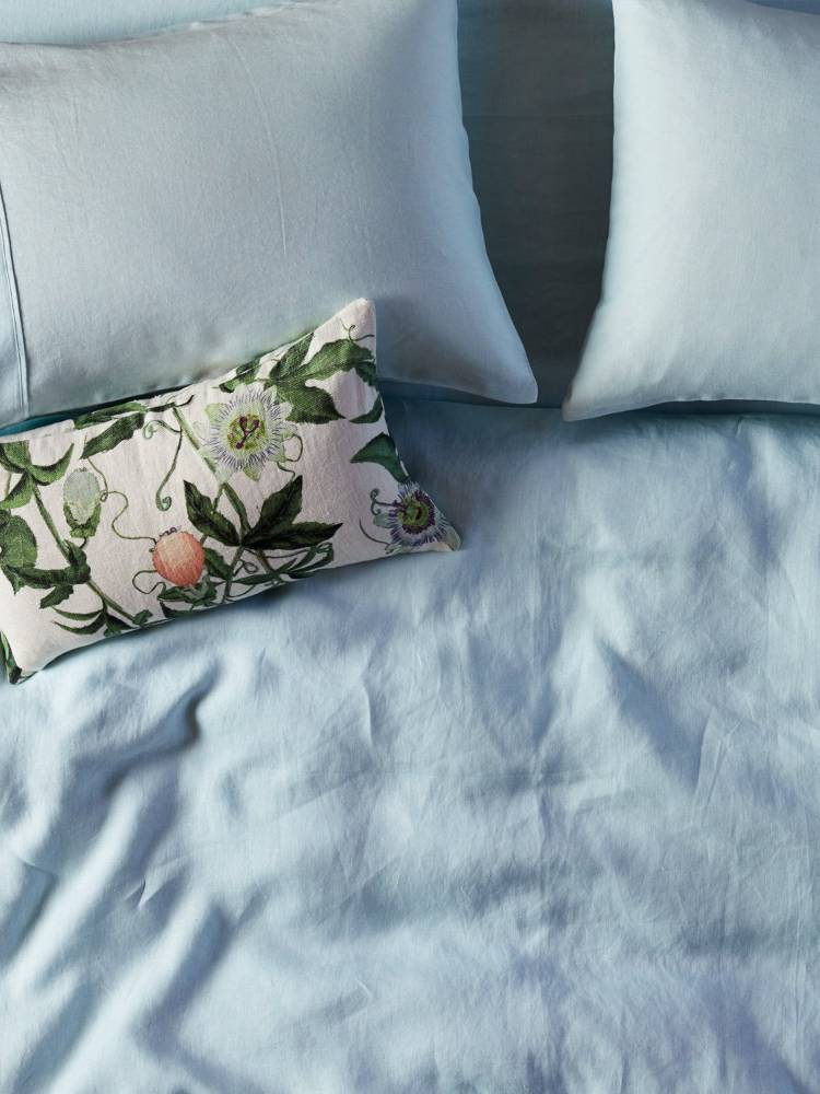 Close up of bed with pale blue kip and co flat sheet