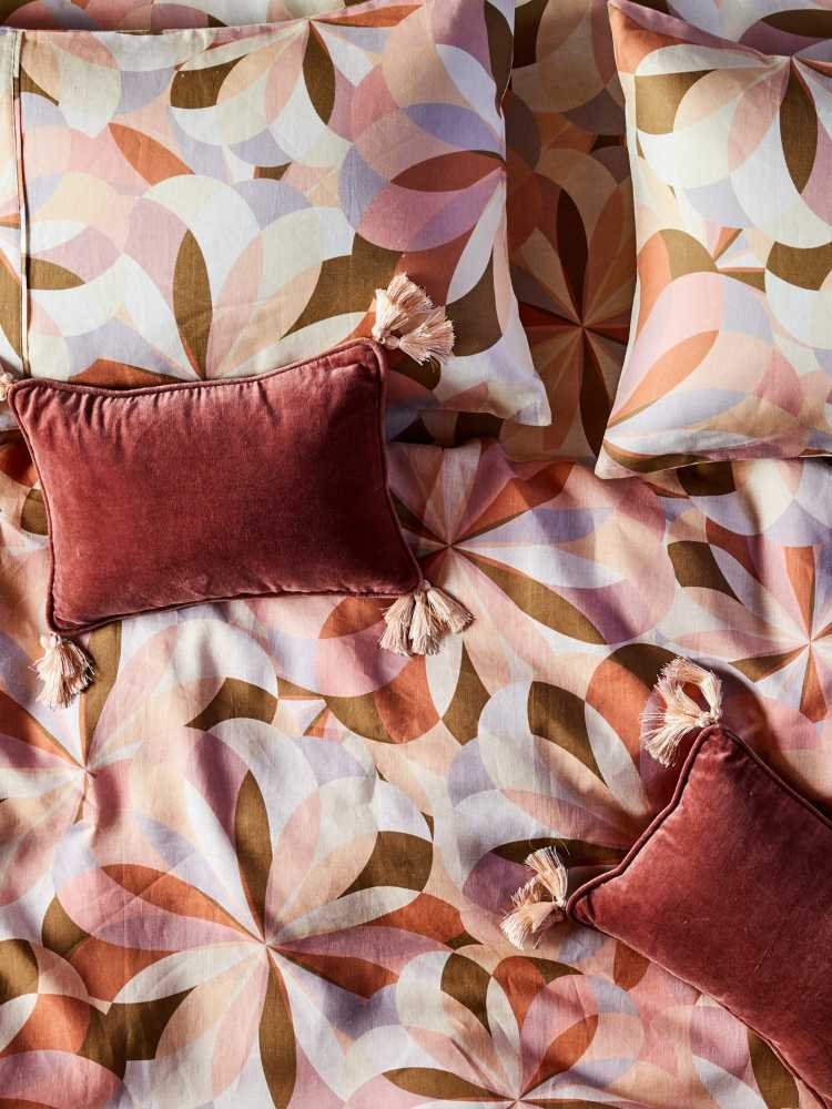 Close of of bed with earthy colour kaleidoscope pattern and burnt red cushion
