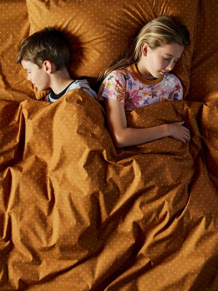 Kids sleeping in bed with mustard poka dot sheets