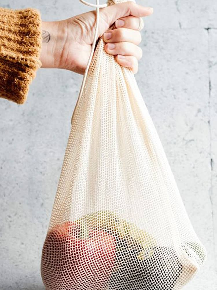 Kappi mesh grocery bag holding apples and avocados