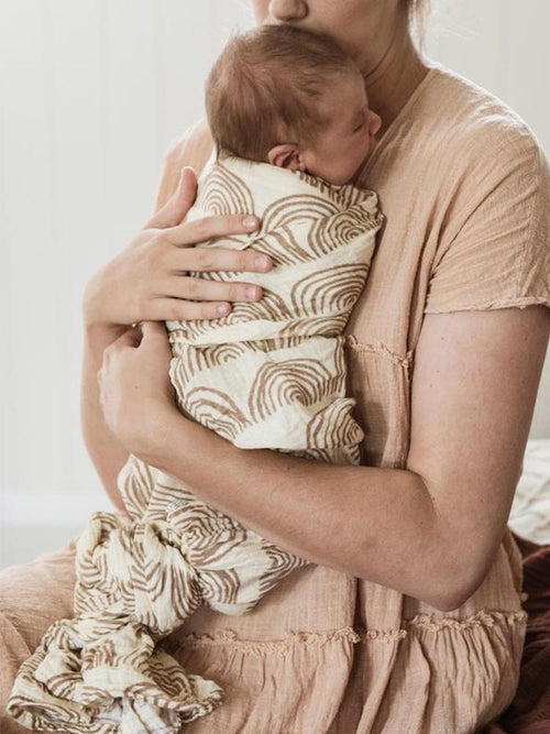 Mother cuddles baby with Kiin Baby Cove Swaddle