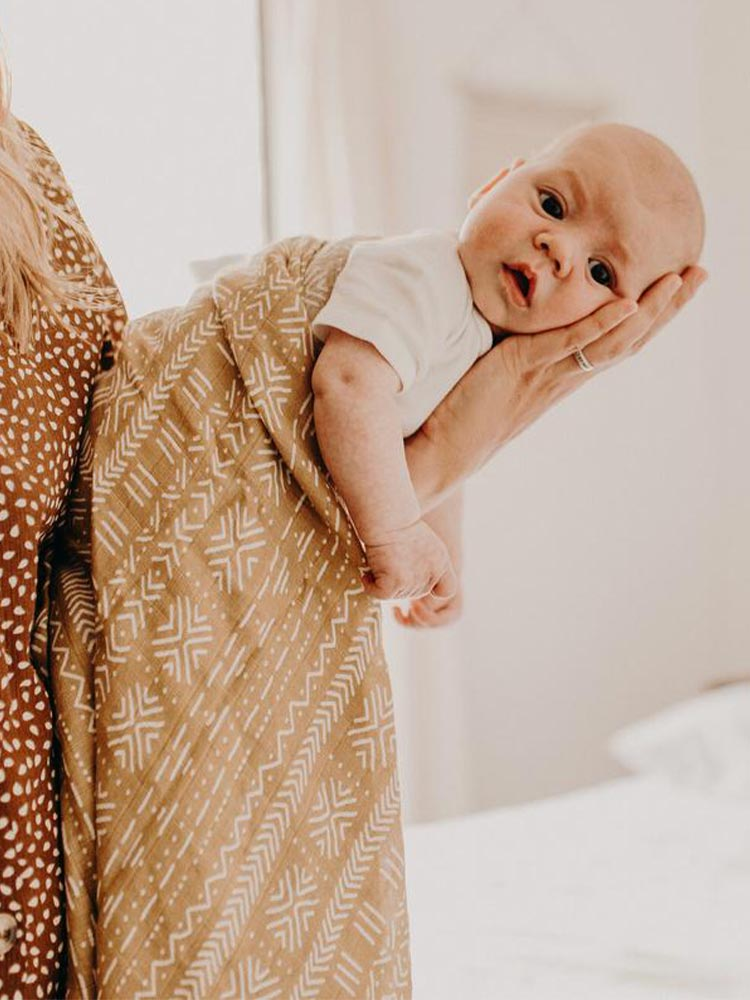 Baby wrapped in Kiin Baby Sand Swaddle