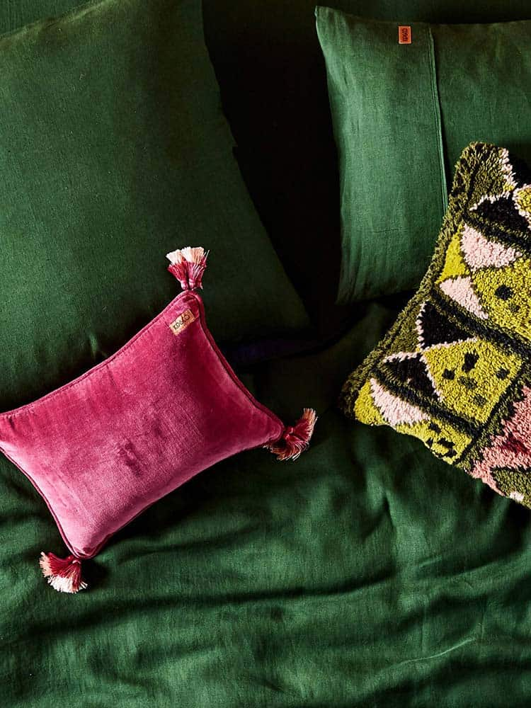 Kip And Co dark pink velvet cushion on green velvet bedding
