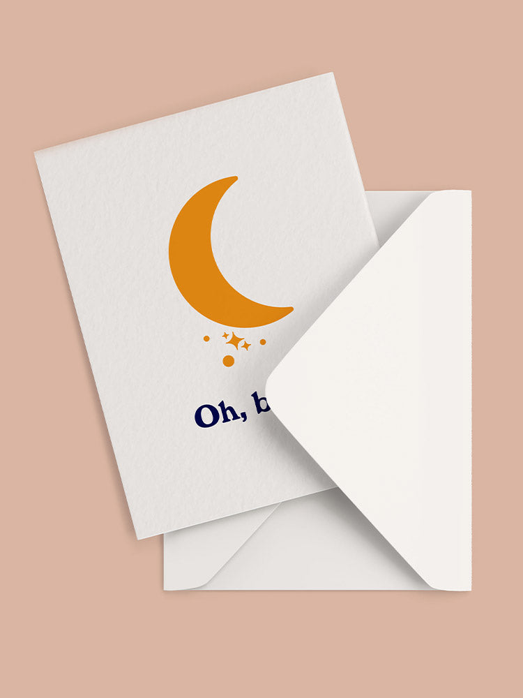 Orange moon graphic on the font of a new baby greeting card with white envelope