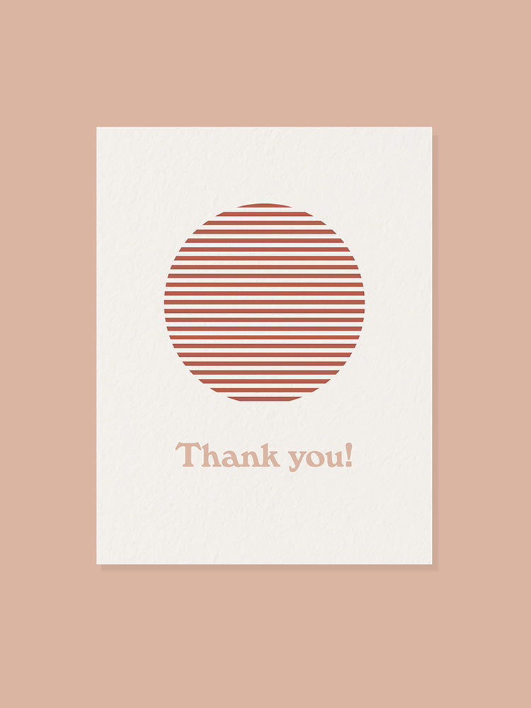 Red sun graphic and thank you text on the front of a greeting card