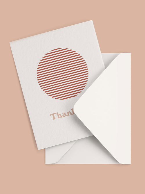 Red sun graphic and thank you text on the front of a greeting card and white envelope