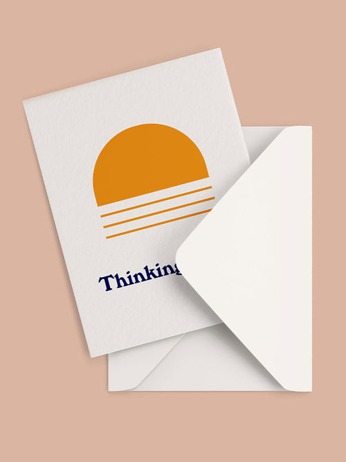 Greeting card with orange arch graphic and thinking of you text and white envelope