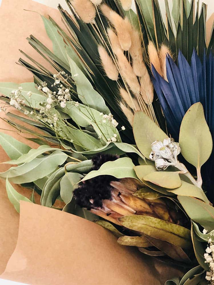 Dried flower arrangement with gum, wheat, cotton, bunny tails and died blue palm fronds