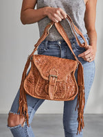 Woman in ripped jeans holds the Ovae Adelaide Woven Saddle Bag in Pecan