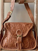 Brown leather cross-hatched bag with front buckle in gold and matching strap