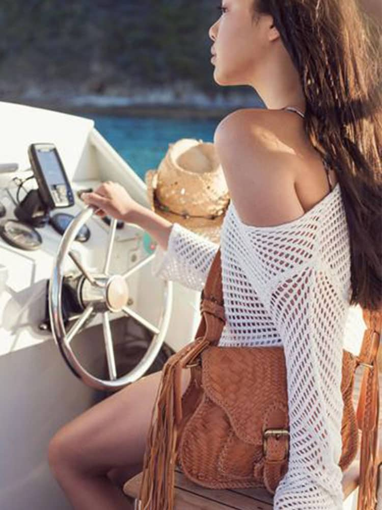 Young bohemian woman drives a boat with the Ovae Woven Saddle bag around her shoulder