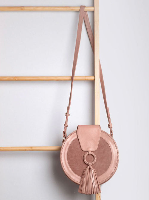 Dusty pink round handbag with matching tassle hangs from a decorative ladder