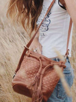 Woman wearing the Ovae Valentina bag in long, dry grass