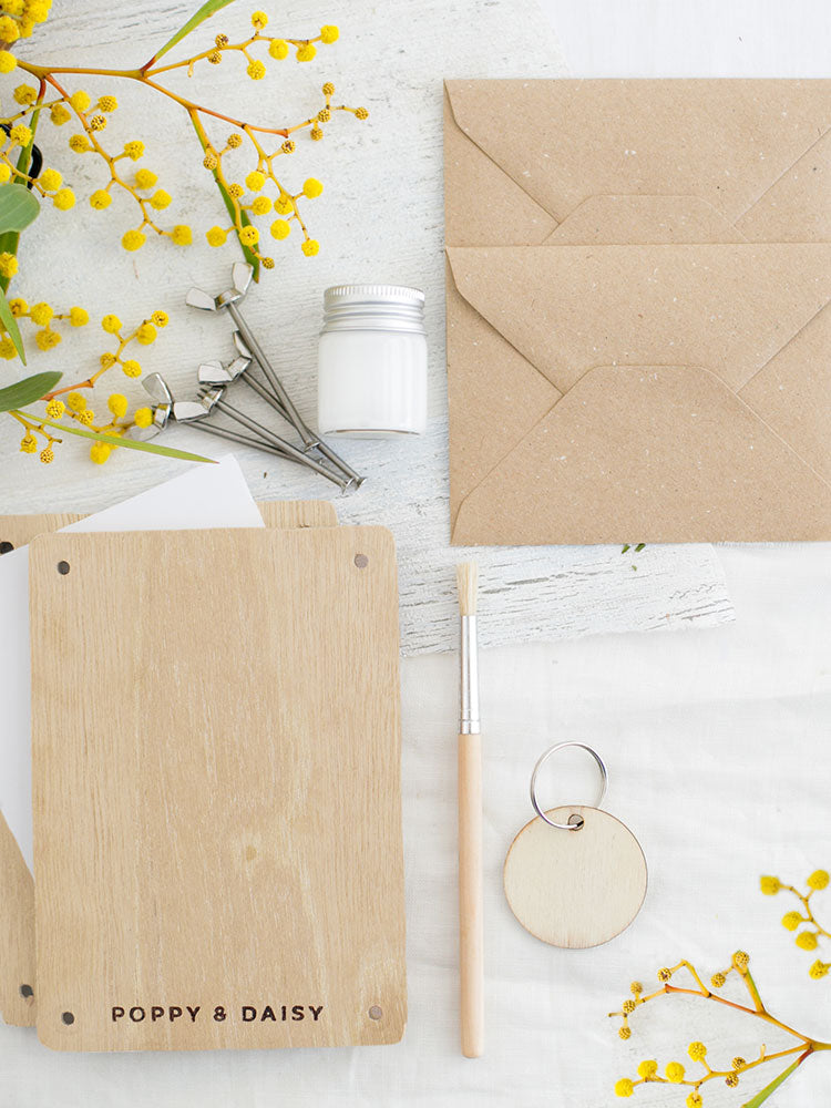 Flat lay with craft paper envelopes, pain brush, wooden flower press frames and yellow wattle