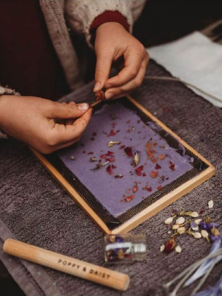 Young girl arranges petals onto purple paper