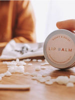 Lip balm tin on it's side being help by a finger