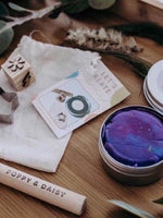 Tin of purple playdough with wooden tools and calico bag