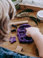 Child makes shapes in purple playdough
