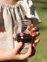 Girls hand holding a glass jar with mini garden