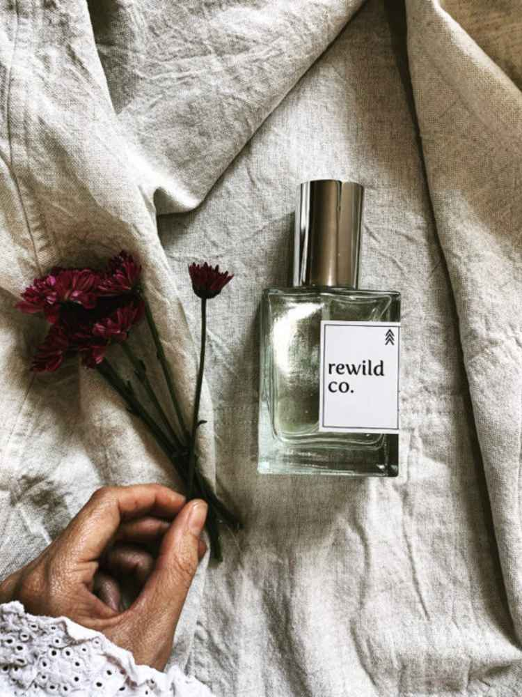 beautiful-bottle-of-perfume-on-soft-linen-with-flowers