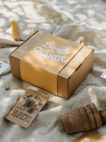 Kraft box with yellow label on linen picnic rug