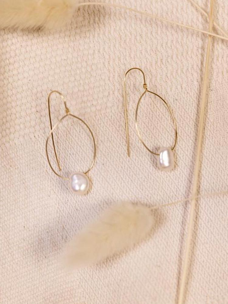 Delicate gold oval hoop earrings with a small pearl