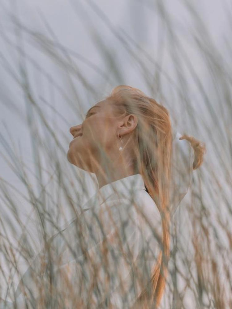 Dreamy scene in long grass of a woman in white wearing the Siren and Stone Harper earrings