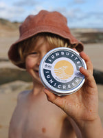 Young boy holding Sunbutter Skincare SPF50 Water Resistant Reef Safe Sunscreen