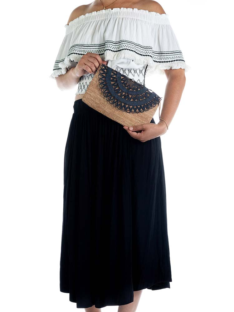 Woman carries the Tanora Boka clutch in Black tea colour