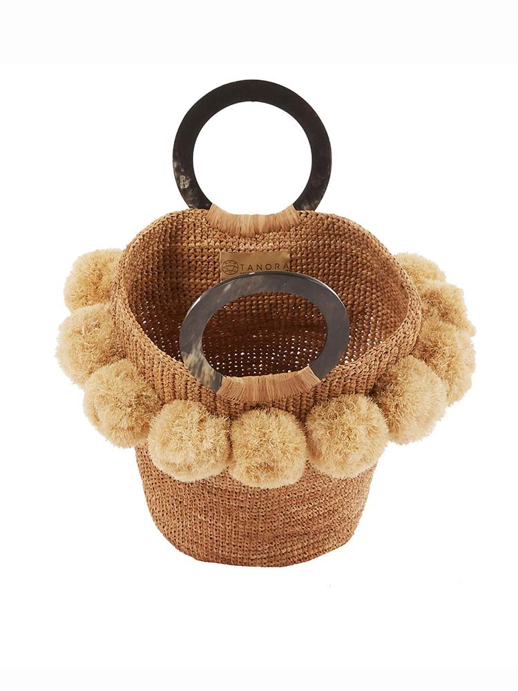 Rattan tote bag with black circular handles and natural pom poms around the top