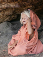 Kids beach poncho in salmon pink with a hood and fringed edges