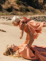 Mother and baby wear matching salmon pink beach ponchos on the sand