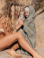 Mother comforts child wearing an olive green beach ponchos on the sand