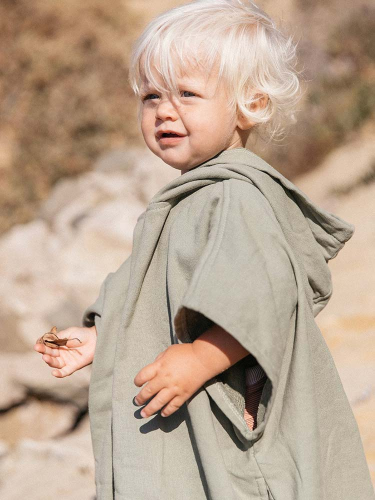 Young child wears an olive green fringed poncho on the beach