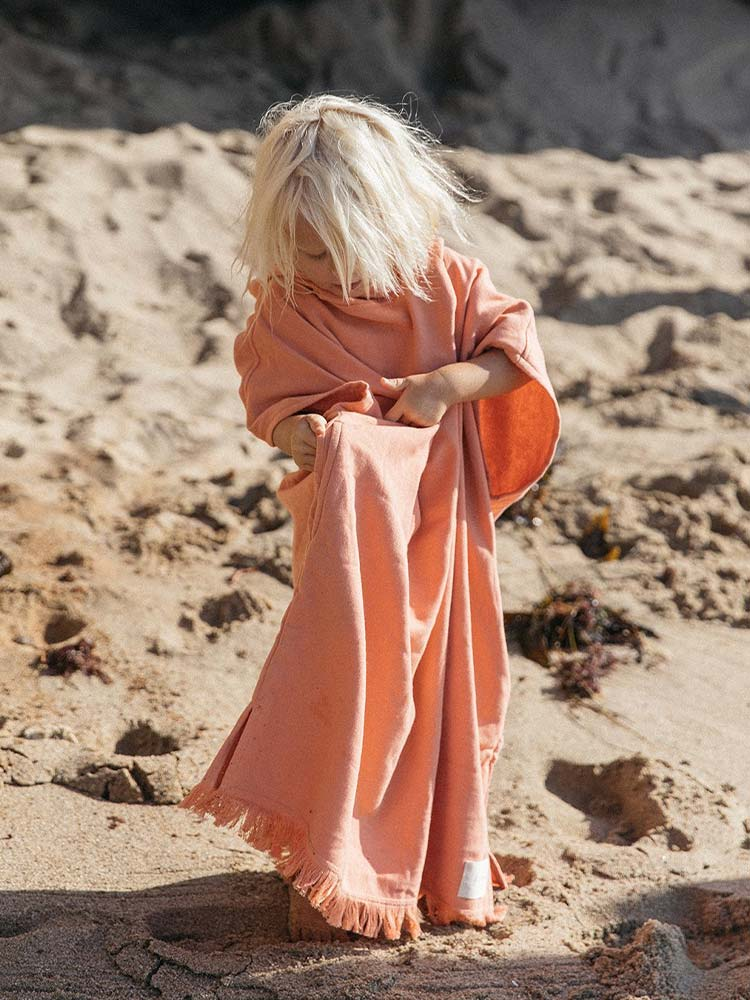 Young child wears a salmon pink fringed poncho on the beach