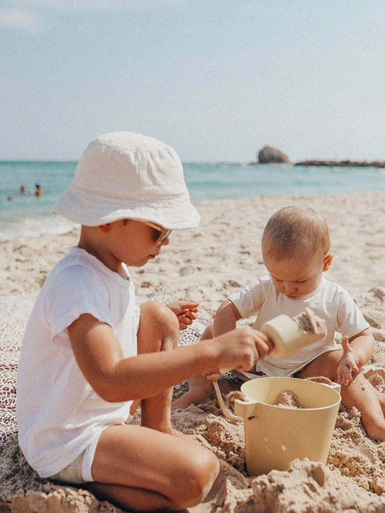 Two young boys play on the beach with their yellow bucket and shovel