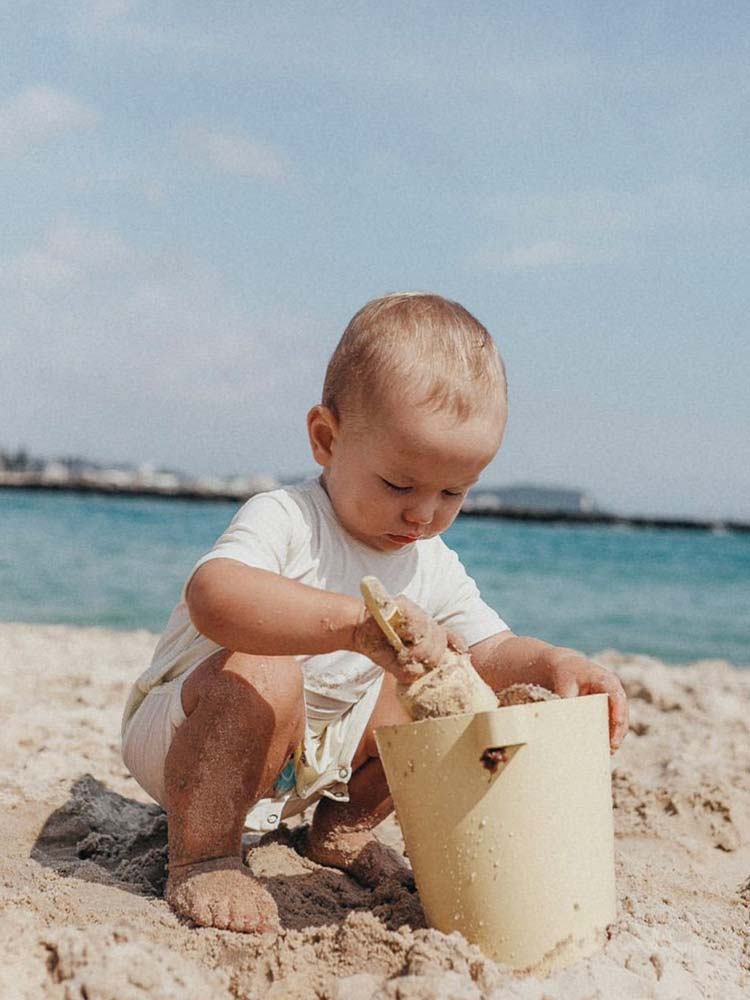Young boy plays with his yellow shovel and bucket on the sand