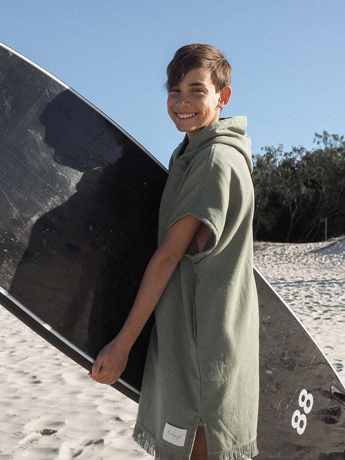 Young boy holds his surfboard in a moss green beach poncho