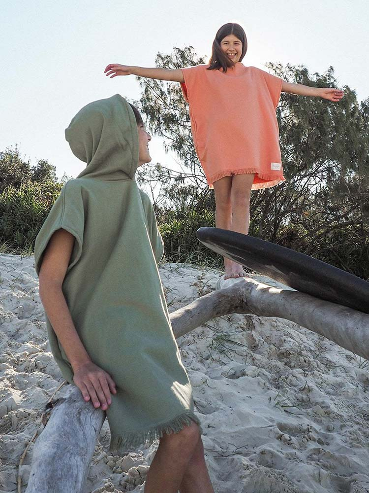Boy and girl wearing beach ponchos play on the beach